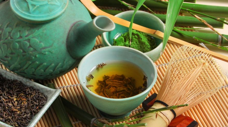 Turquoise teapot and mug of green tea with bamboo