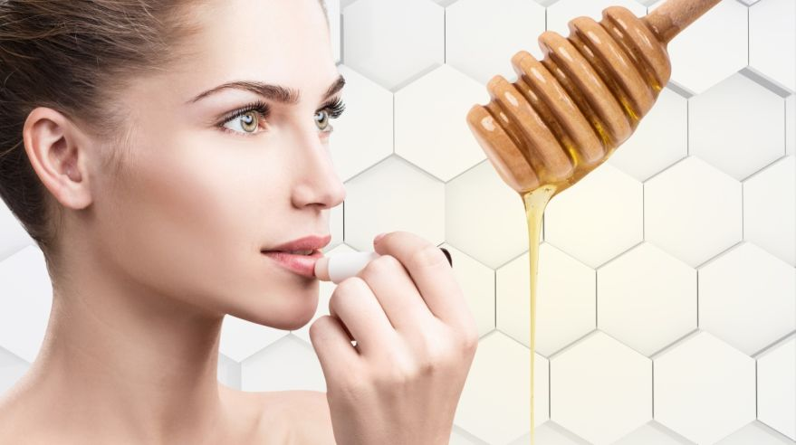 Young woman putting lipbalm with honey on lips.