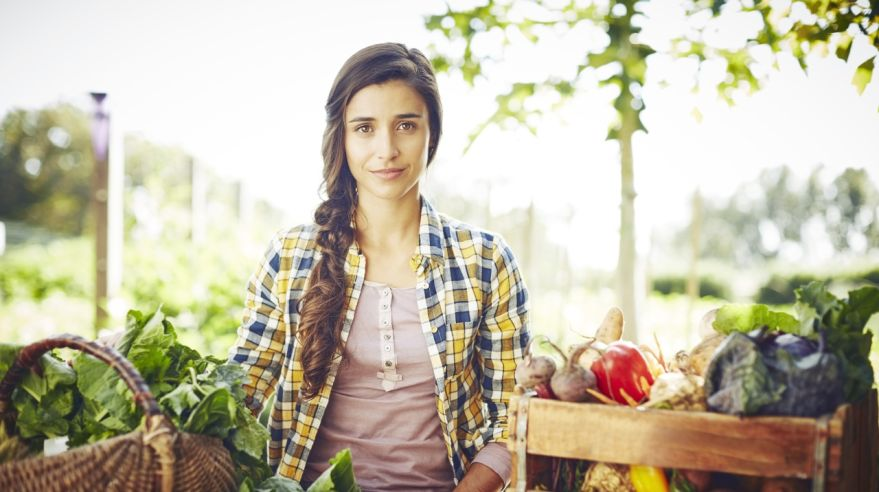 Portrait of beautiful woman standing with vegetables in containe