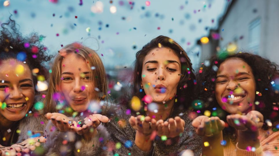 Young women blowing confetti from hands.