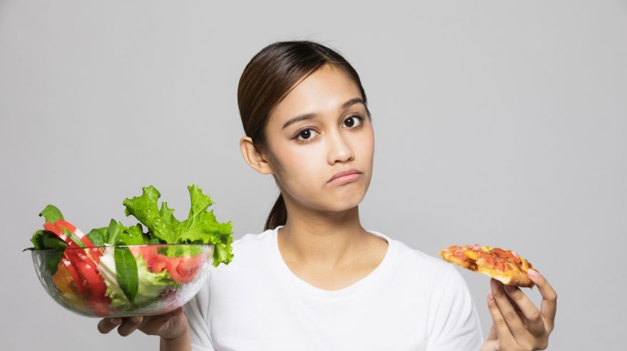 Young woman holding salad bowl and pizza.