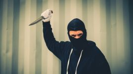 portrait of criminal or bandit wear black mask holding a knife and looking to camera, concept of cutthroat and assassin