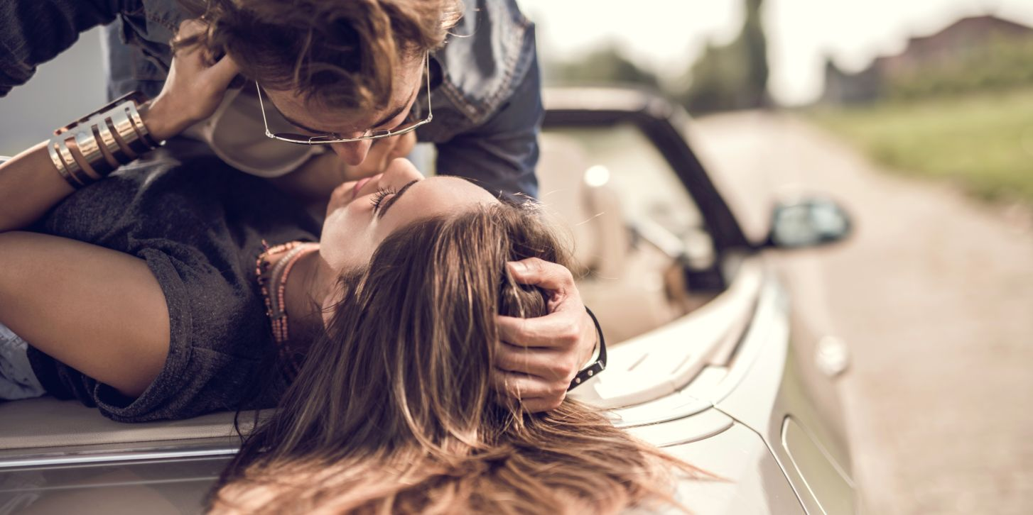 Young romantic couple enjoying in their love on a convertible.